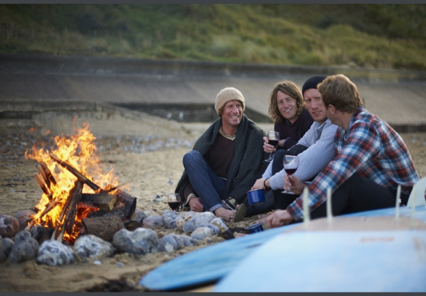 Friends gathered on beach around fire.