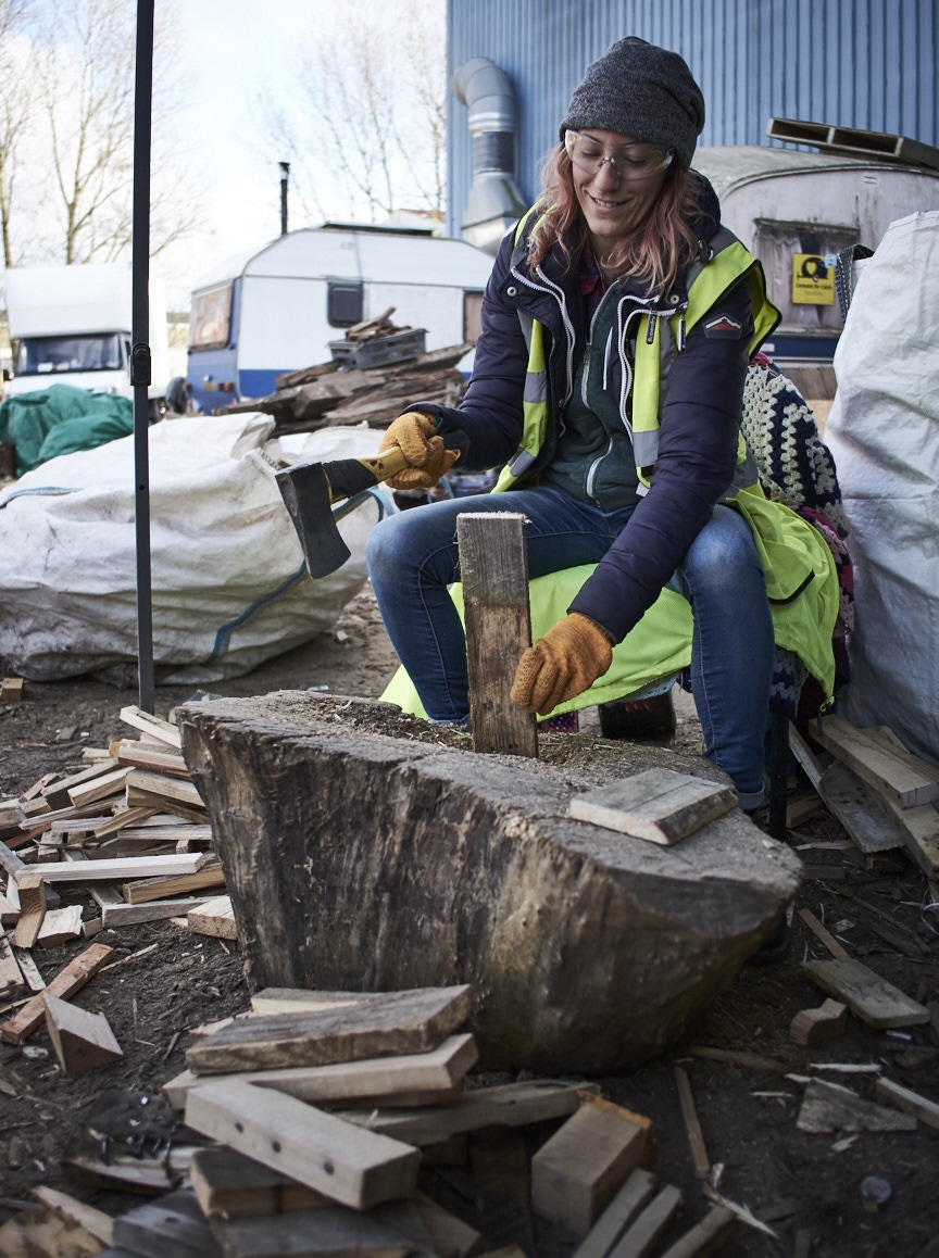 Volunteer chopping wood for Calais refugees.