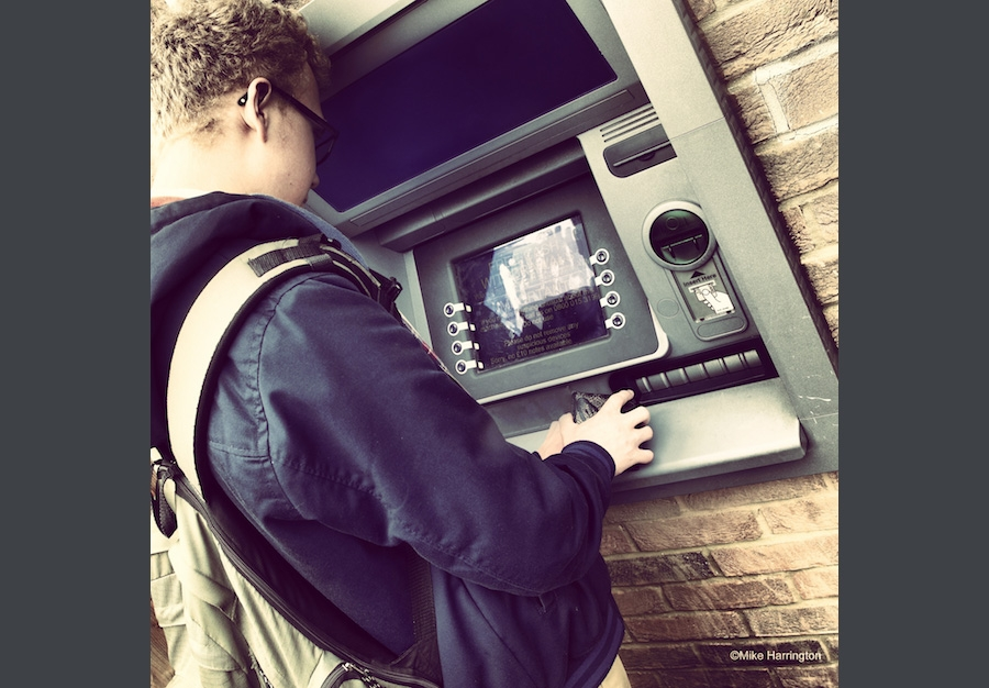 Covering keypad at an ATM with hands.