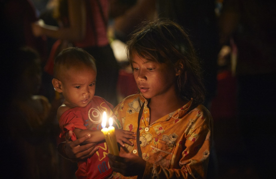 Girl holding small child and candles.