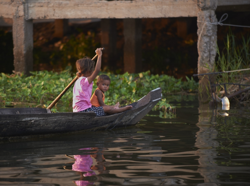 Children rowing boat in floating village in Siem Reap, Cambodia.