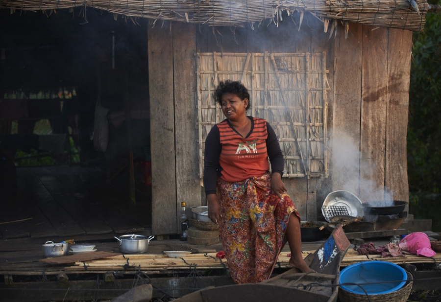 Woman cooking at home in floating village in Siem Reap.
