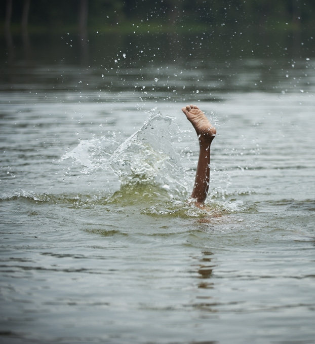 Boy playing in river in Cambodia. Foot sticking out of water.