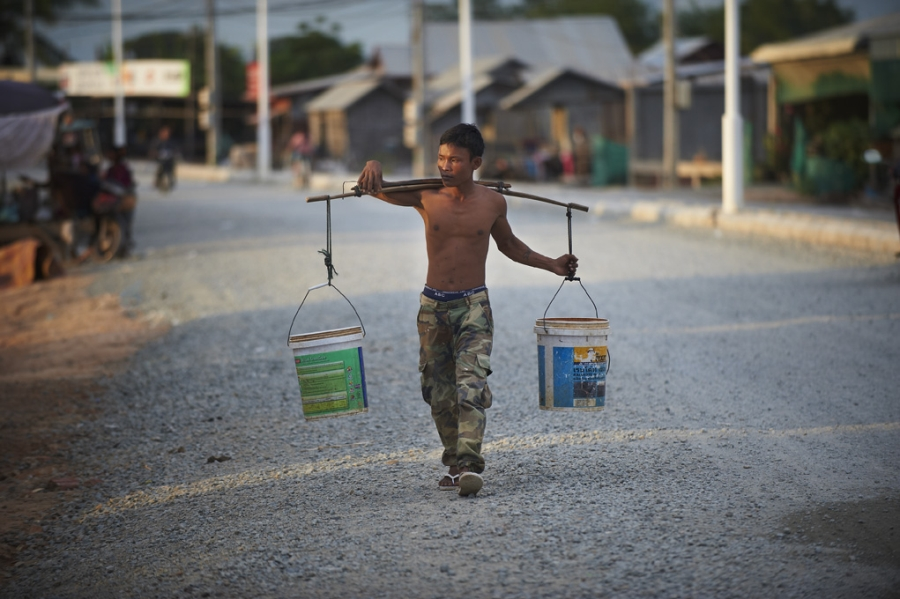 Man carrying water on his shoulders in Cambodia.