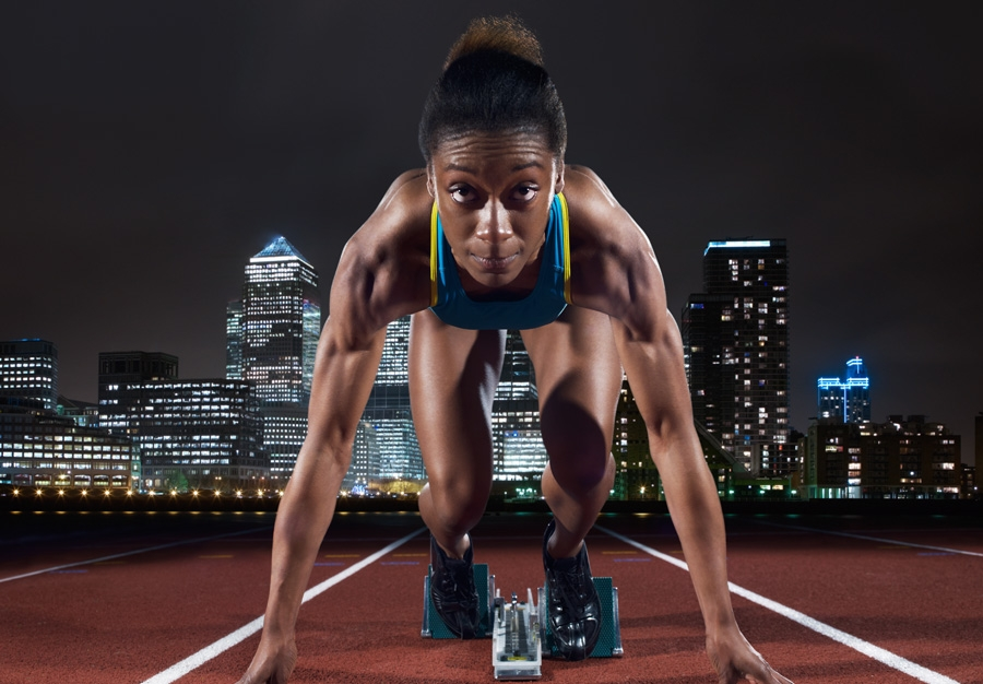 Hurdler in starting position against backdrop of London's Canary Wharf.