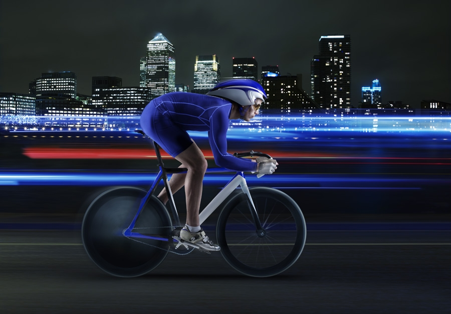 Cyclist performing against backdrop of Canary Wharf.