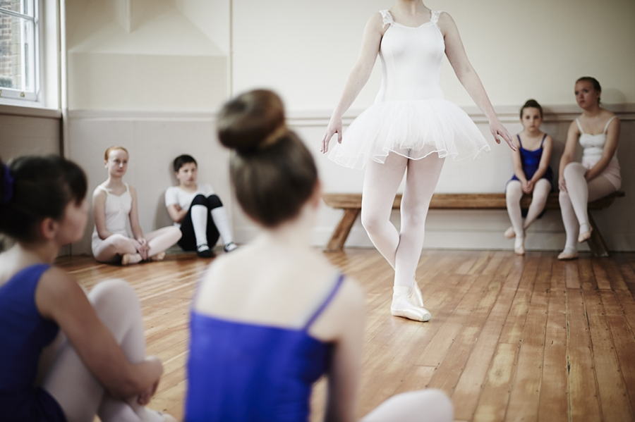 Ballet pupils sit around a performing fellow pupil in class.