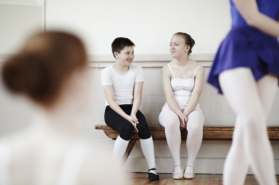 Two ballet pupils converse during a break in their class.