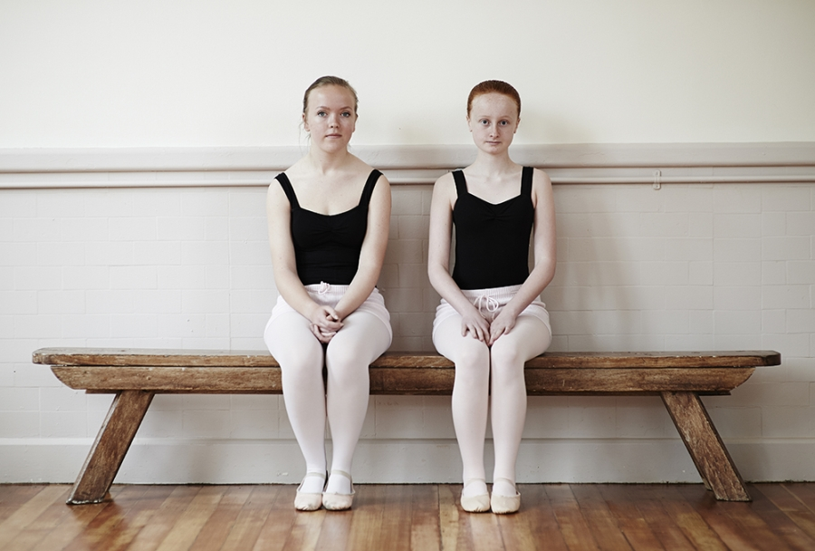 Two female ballet pupils on bench looking to camera.