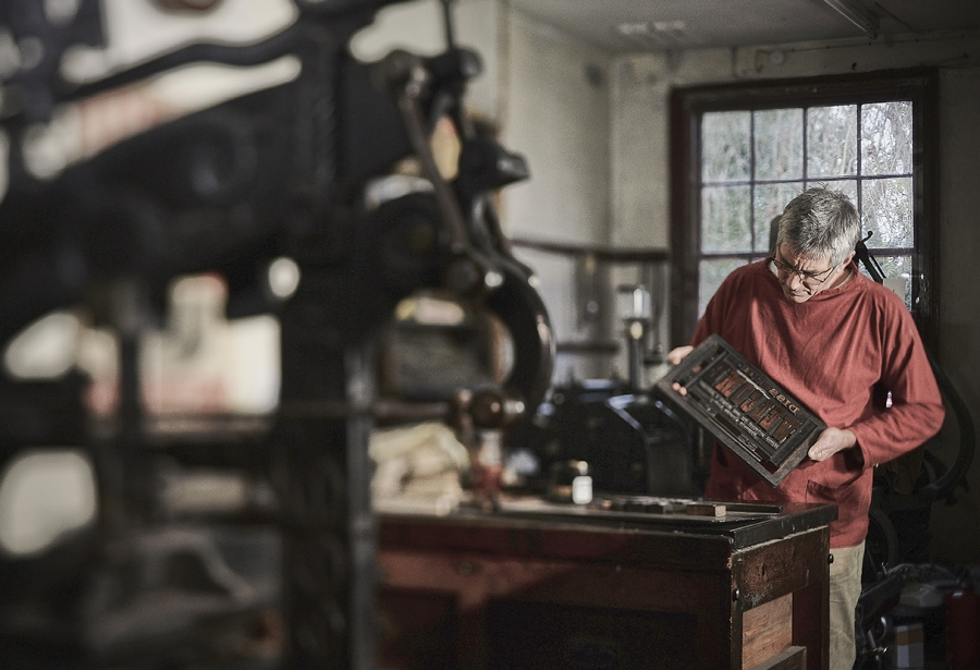 Man setting letterpress.