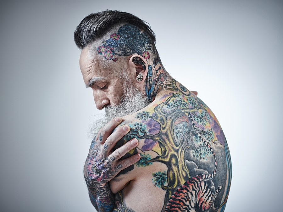 Middle aged male showing extensively tattooed body.