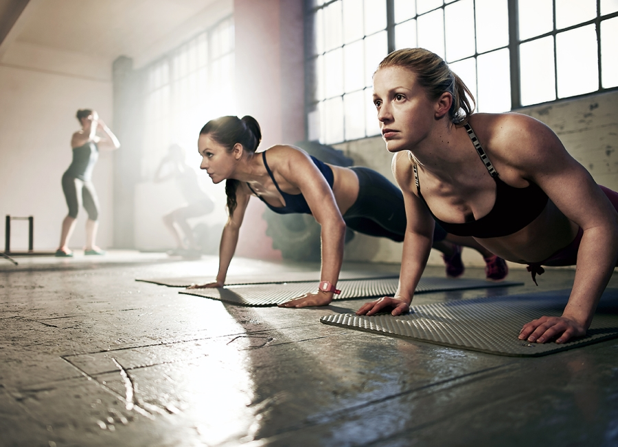 Women doing press-ups in city gym.