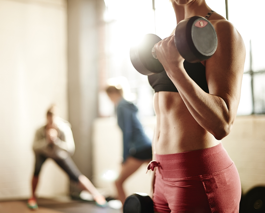 Women using dumbbells in urban gym.
