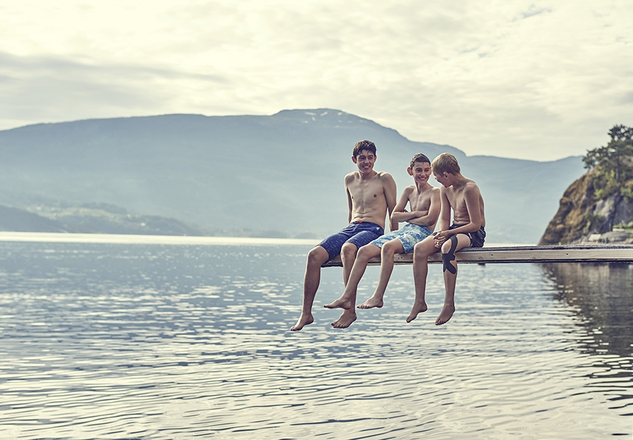 Young Males talking on Diving Board over Norwegian Fjord