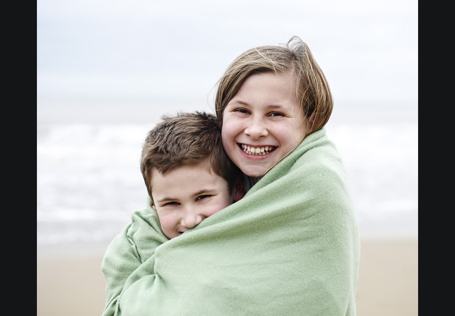 Young boy and girl wrapped up in towel