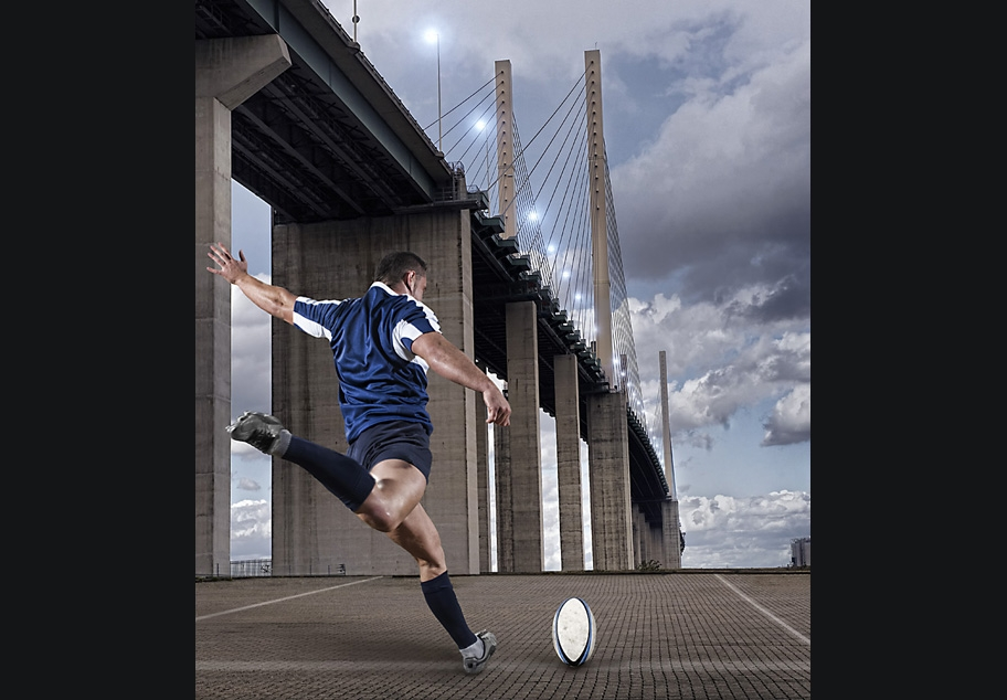 Rugby player kicking ball over bridge