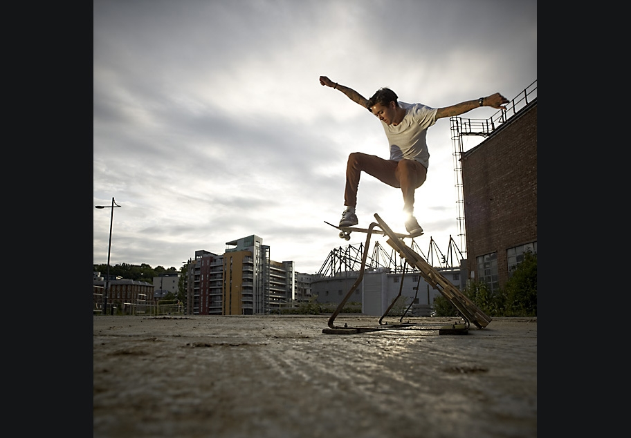 Skateboarder jumping over ramp