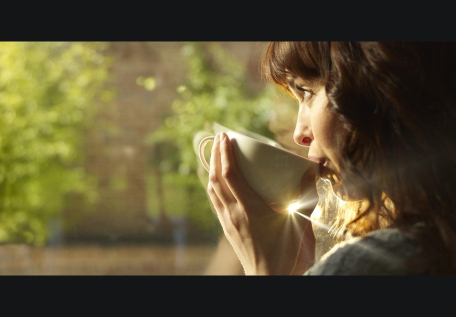 Female drinking coffee looking out of window
