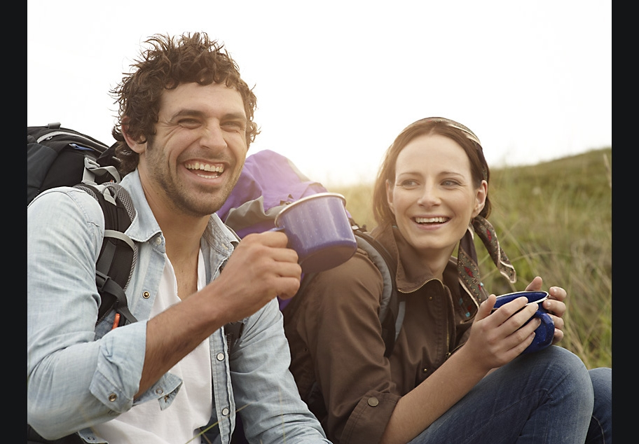 Male and female hikers drinking a cup of coffee