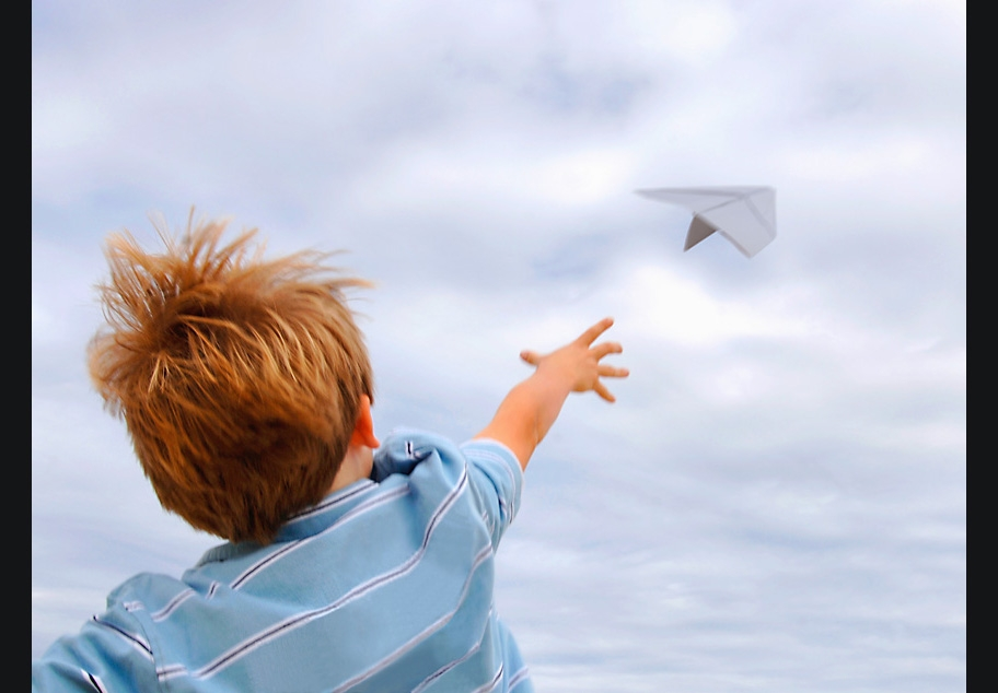 Young boy flying paper airplane