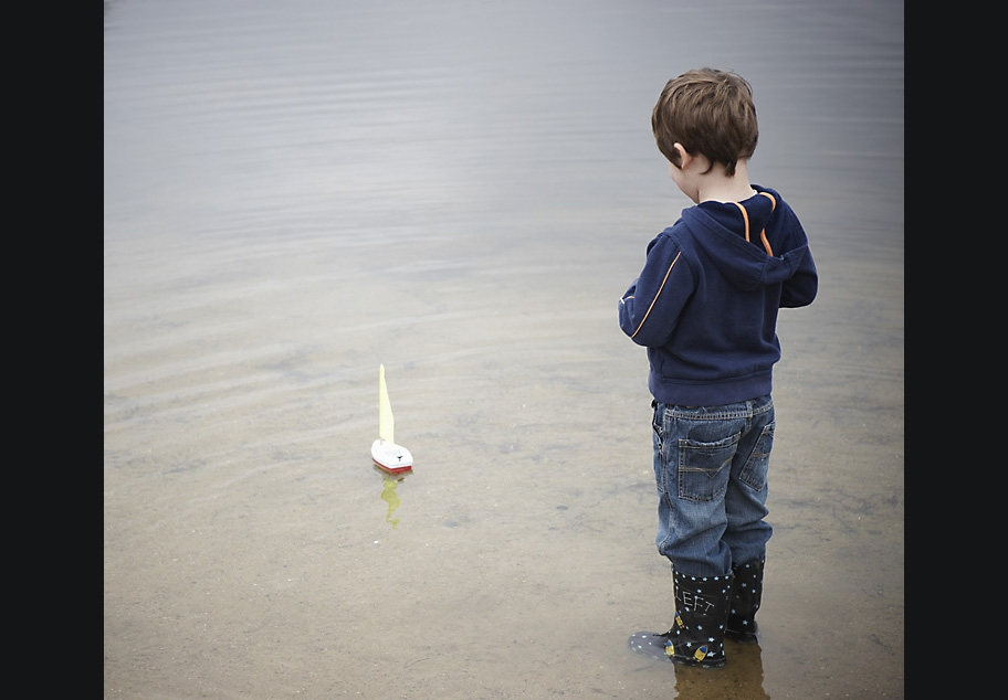 Young boy sailing toy boat on pond