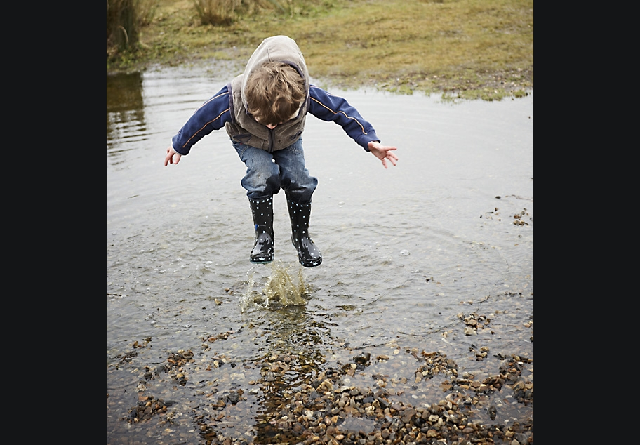 Young boy jumping huge puddle