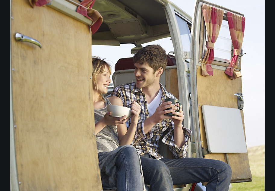 Male and female sitting in camper van with a cup of coffee