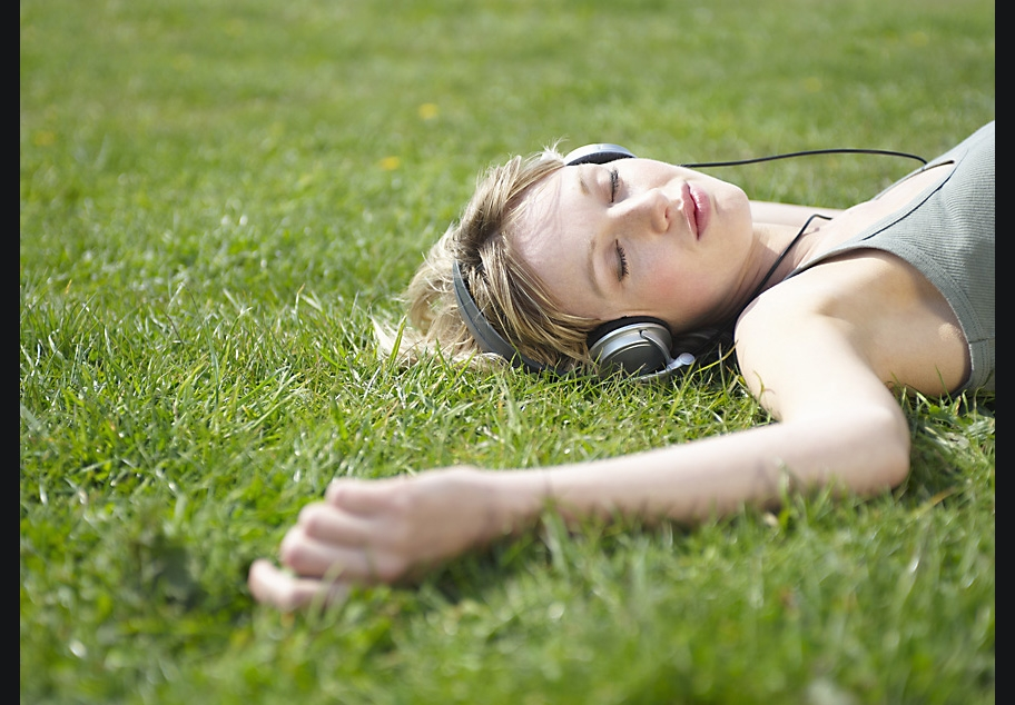 Female laying on grass with headphones on listening to music