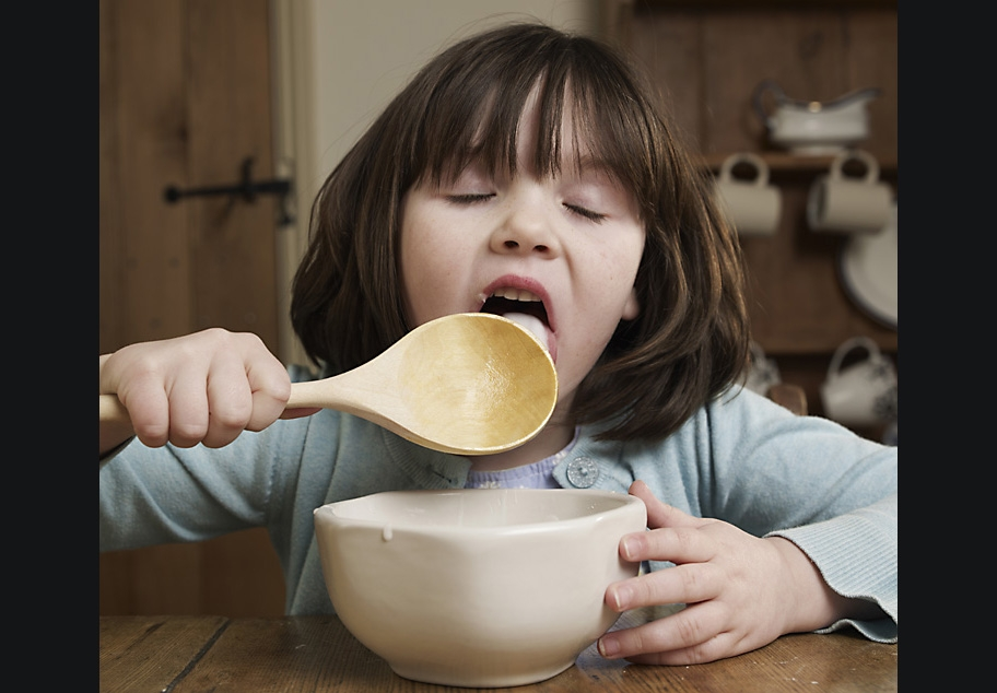 Young girl licking cake mixture off wooden spoon