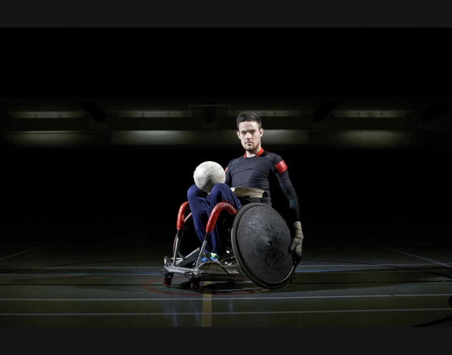 Wheelchair Rugby Player with ball in lap.